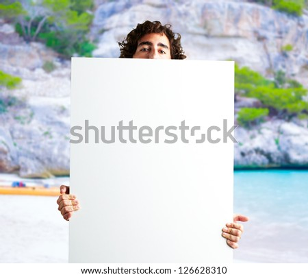 Portrait Of Man Holding a blank billboard at the shore, outdoor - stock photo