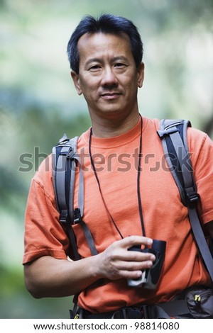 Portrait of man holding binoculars while hiking