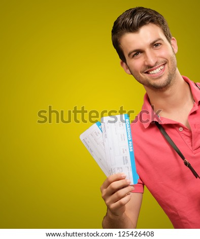 Portrait Of Man Holding Boarding Pass On Yellow Background - stock photo