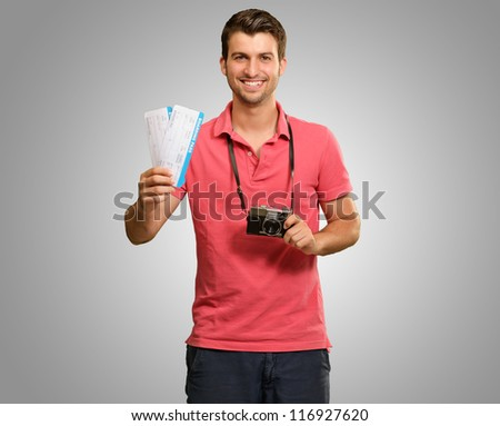 Portrait Of Man Holding Camera And Boarding Pass On Grey Background