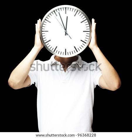 portrait of man holding clock against a black background