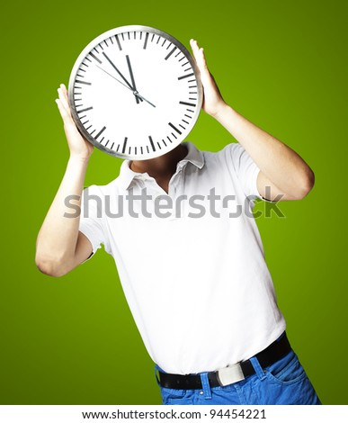 portrait of man holding clock against a green background - stock photo