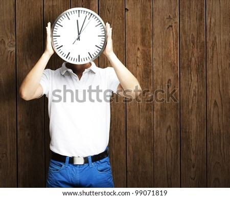 portrait of man holding clock against a wooden wall