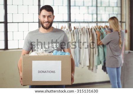 Portrait of man holding clothes donation box with woman seen in background at office