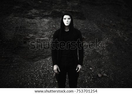 Portrait of man in black hoodie wearing white anonymous mask