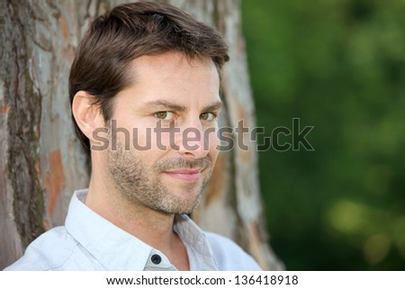 Portrait of man in front of tree trunk