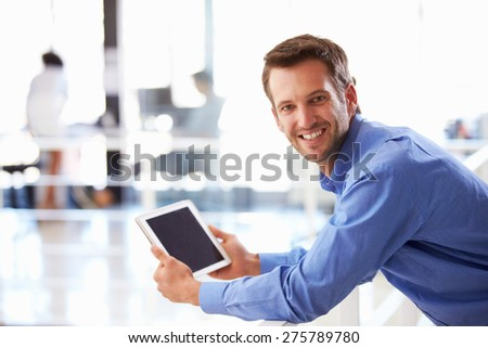 Portrait of man in office using tablet - stock photo