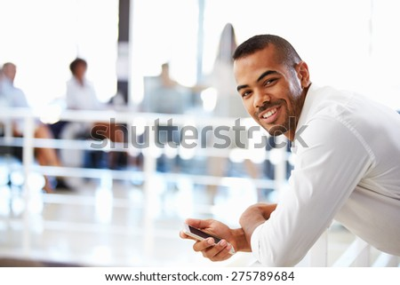 Portrait of man in office with telephone, smiling - stock photo