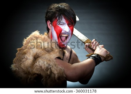 Portrait of man in war paint, with an ax in his hands, a warrior brandishing an ax furiously screaming, barbarian of ancient times, Viking and savage. - stock photo