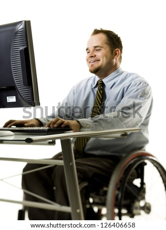 Portrait of man in wheelchair working with computer - stock photo