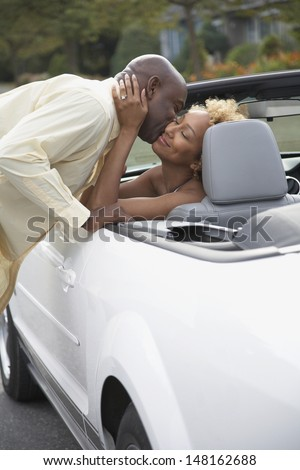 Portrait of man kissing wife in car