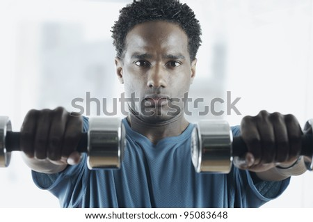 Portrait of man lifting weights - stock photo