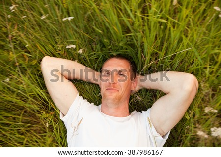Portrait of   man lying on   green summer meadow.