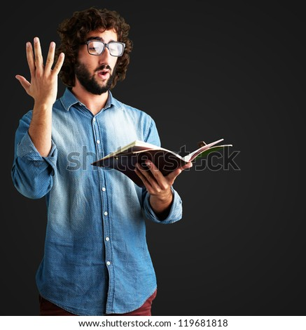 Portrait Of Man Reading Book against a black background - stock photo