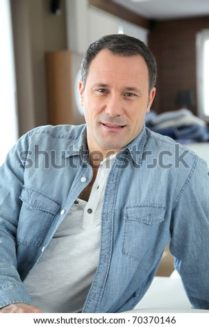 Portrait of man sitting in living room - stock photo