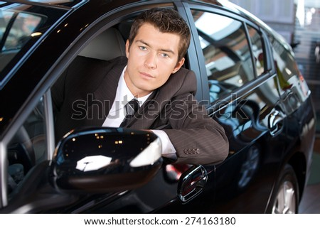 Portrait of man sitting in new car - stock photo