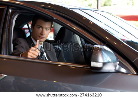 Portrait of man sitting in new car showing thumbs up - stock photo
