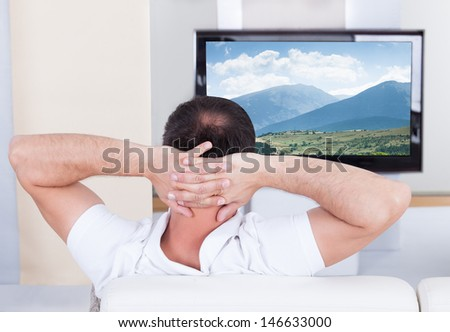 Portrait of man sitting on couch watching television - stock photo