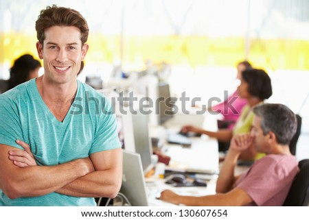 Portrait Of Man Standing In Busy Creative Office - stock photo