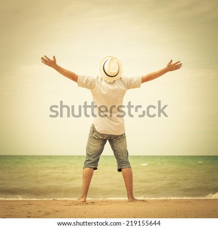 portrait of  man standing on the beach at the day time and raising hands  - stock photo