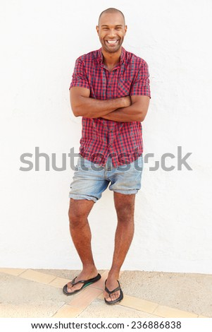 Portrait Of Man Standing Outdoors Against White Wall - stock photo