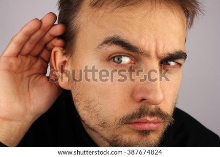 portrait of man, that  listens carefully, putting a hand to his ear