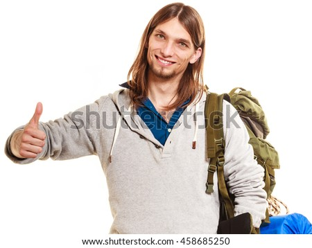 Portrait of man tourist backpacker on trip showing thumb up gesture. Young guy hiker backpacking. Summer vacation travel. Studio shot. Isolated on white background.