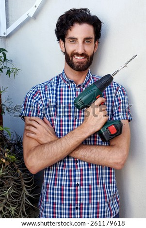 portrait of man using cordless battery drill for outdoor home improvements - stock photo