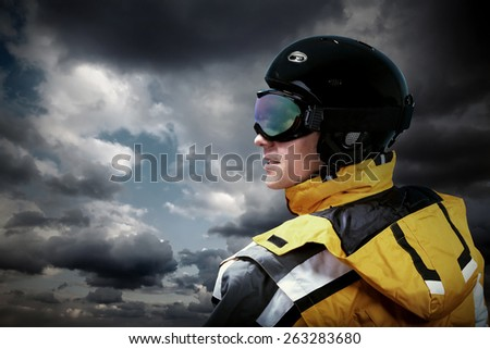 Portrait of man wearing a helmet and glasses on the background of sky with clouds - stock photo