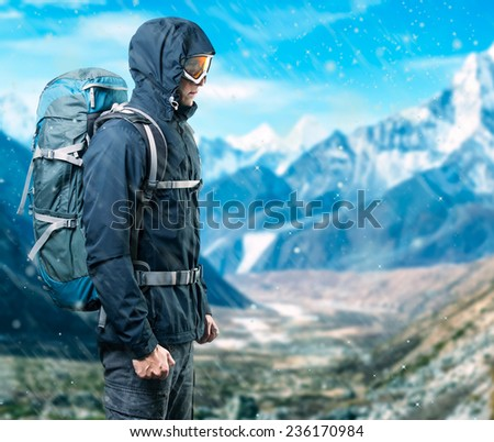 Portrait of man with backpack on the background of snow mounts - stock photo