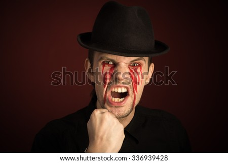 portrait of man with bloody tears on burgundy background