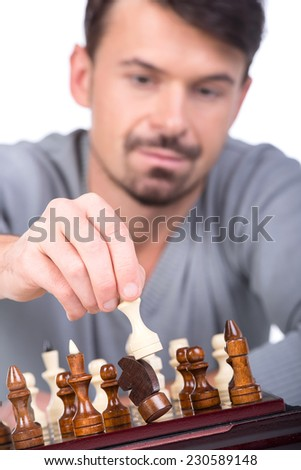 Portrait of man with chess is making the move on the white background. - stock photo