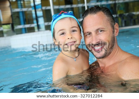 Portrait of man with cute little boy in swimming pool - stock photo