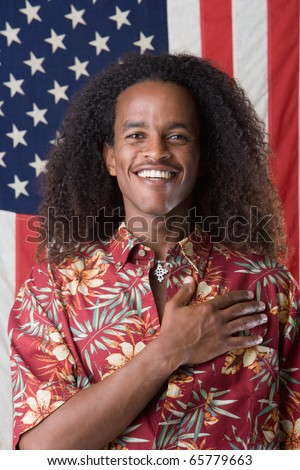 Portrait of man with hand over heart standing in front of American flag