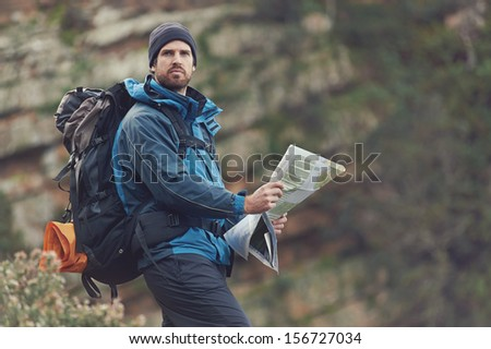 Portrait of man with map in wilderness mountains - stock photo