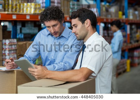 Portrait of managers are working with a tablet in the middle of cardboard boxes in a warehouse