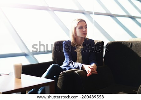 Portrait of managing young woman having coffee time sitting in big bright office next to the window, soft focus, filtered image with flare sun light from the window - stock photo