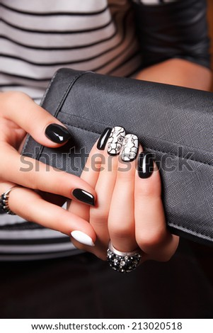Portrait of manicured nails with nail polish holding a wallet - stock photo