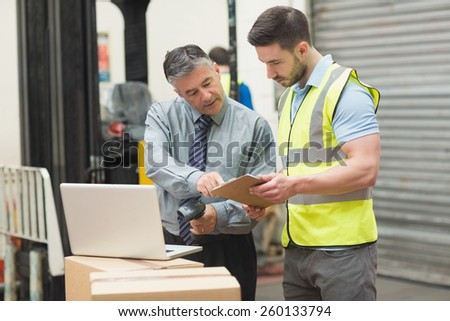 Portrait of manual workers scanning package in the warehouse - stock photo
