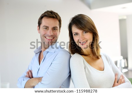 Portrait of married couple standing with arms crossed - stock photo