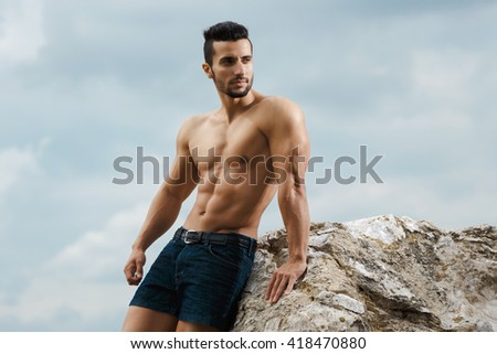 Portrait of masculinity. Shot of a handsome shirtless muscular man relaxed posing looking away outdoors. - stock photo