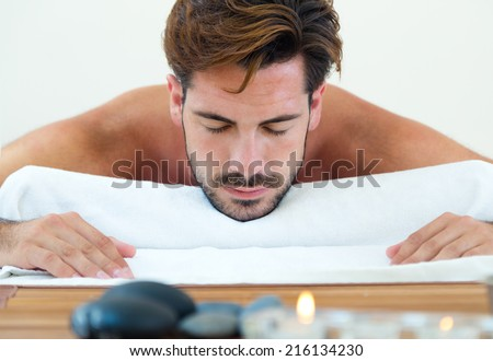 Portrait of masseur doing massage on man body in the spa salon. - stock photo