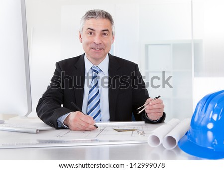 Portrait Of Mature Architect Male With Blueprint In The Office - stock photo