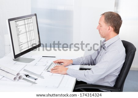 Portrait Of Mature Architect Using Computer At Office Desk - stock photo
