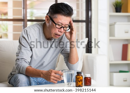 Portrait of mature Asian man having headache, sitting on sofa at home, senior retiree indoors living lifestyle.