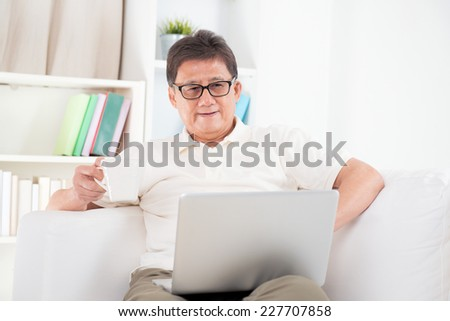 Portrait of mature Asian man using computer laptop, enjoying cup of coffee in morning, sitting on sofa at home, senior retiree indoors living lifestyle.