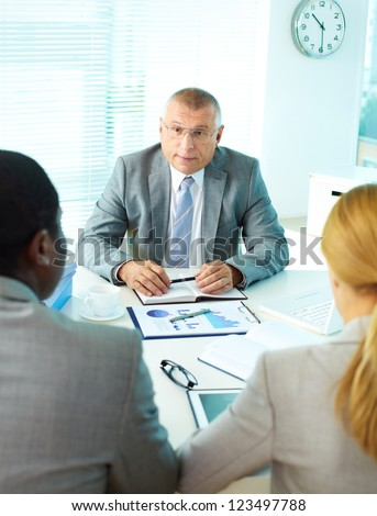 Portrait of mature boss looking at his employees at meeting - stock photo