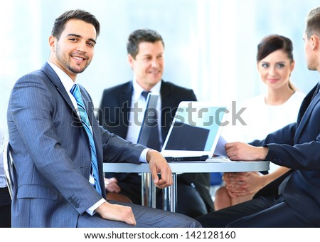 Portrait of mature business man smiling during meeting with colleagues in background - stock photo