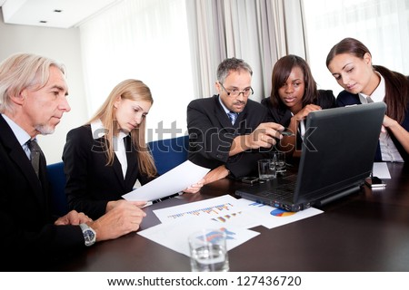 Portrait of mature business manager pointing towards his laptop and discussing with colleagues together in office