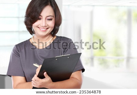 portrait of mature Business woman holding a clipboard